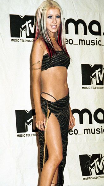 VMA Fashion | Barely There - 09.07.2000, New York City, NY: Christina Aguilera unleashes her inner belly dancer, baring nearly all in a glittery midriffer and a skin-tillating wrap skirt.