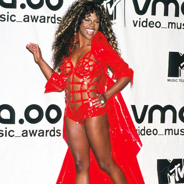 VMA Fashion | Barely There - 09.07.2000, New York City, NY: What?! Oh, yeah, we were looking at her hair. No one can pull off a neon orange plastic teddy quite like Lil' Kim did at the 2000 VMAs.