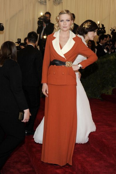 Celebrity Fashion Police at 2012 Met Gala - Kirsten Dunst - Looks a bit wicked in this red skirt-jacket combination that comes with pop out white parachute