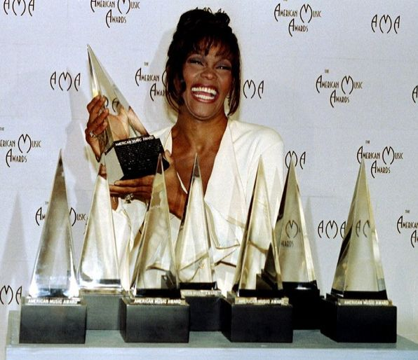 Whitney Houston | Timeline - 1963 to 2012 - Whitney Houston 1994 - shows off the seven awards she won at the 21st American Music Awards.